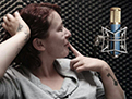 A young woman sings into a microphone in the studio vocal booth as she listens to a backing track on headphones